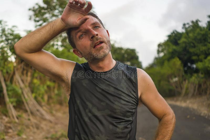 Sport and fitness lifestyle portrait of young attractive sweaty and tired man exhausted after outdoors running workout on. Beautiful country road breathing stock image