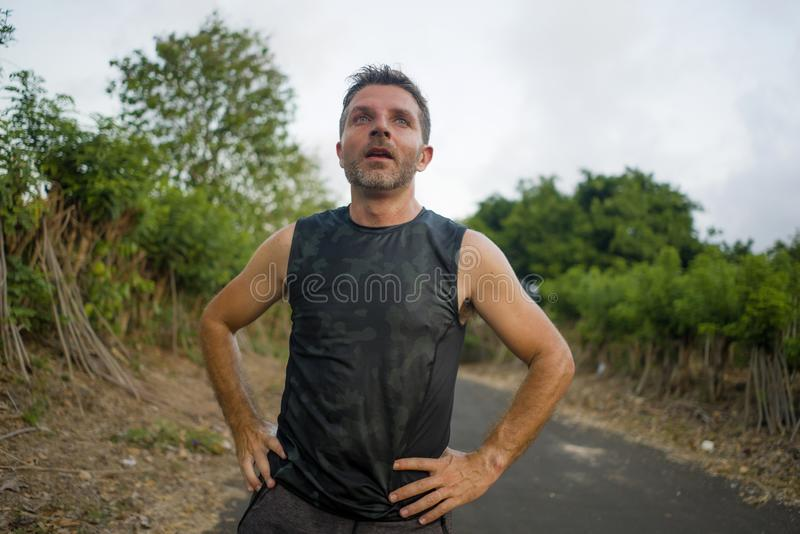 Sport and fitness lifestyle portrait of young attractive sweaty and tired man exhausted after outdoors running workout on royalty free stock photo