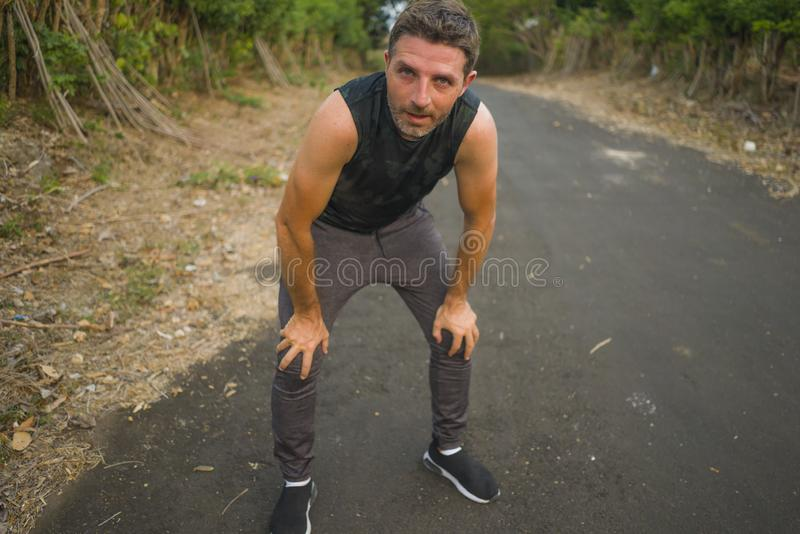 Sport and fitness lifestyle portrait of young attractive sweaty and tired man exhausted after outdoors running workout on. Beautiful country road breathing royalty free stock photos