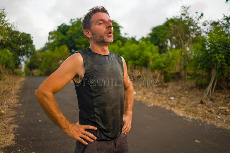 Sport and fitness lifestyle portrait of young attractive sweaty and tired man exhausted after outdoors running workout on stock photography