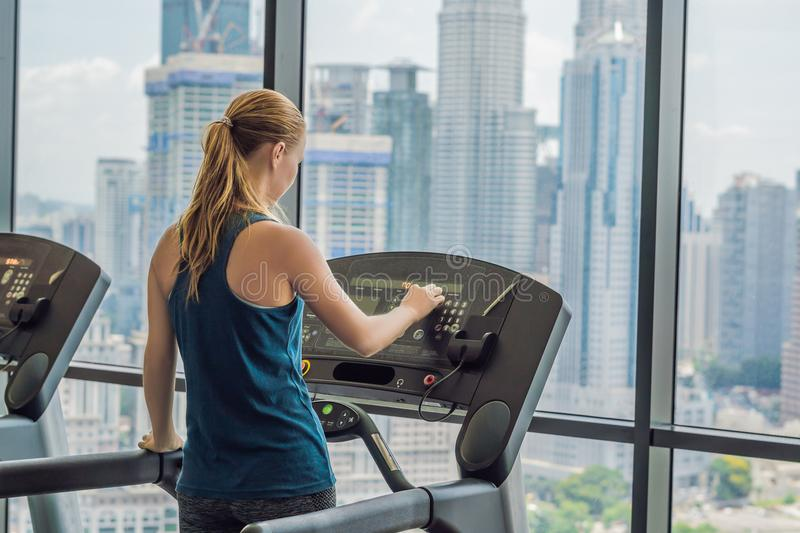 Sport, fitness, lifestyle, technology and people concept - woman exercising on treadmill in gym against the background of a big ci stock photography