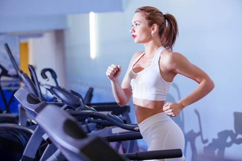 Sport, fitness, lifestyle, technology and people concept - Young woman running on treadmill stock photos
