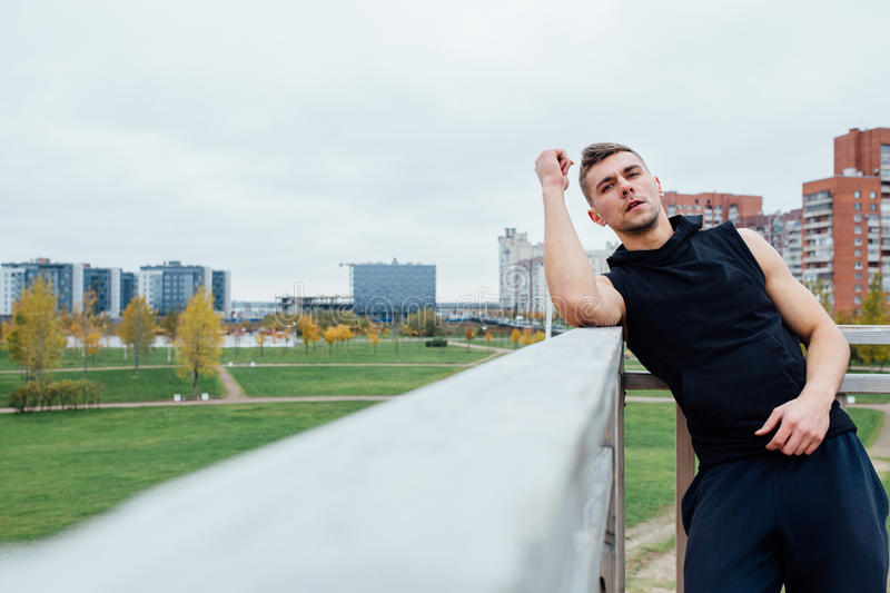 Sport fitness man posing against the backdrop of the city. Male athlete outside fall park. Fit model. stock images