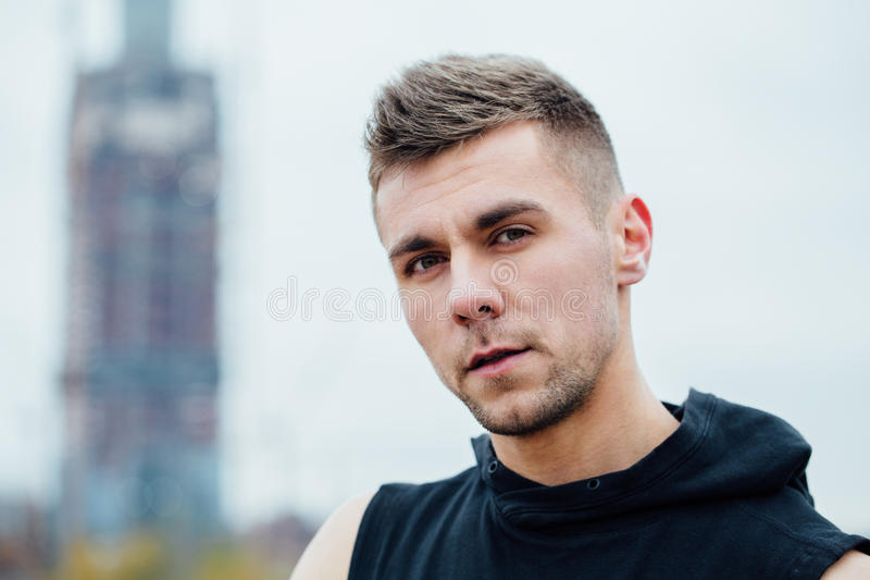 Sport fitness man posing against the backdrop of the city. Male athlete outside fall park. Fit model. royalty free stock photo