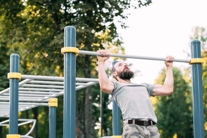 Sport fitness training man pull ups chest muscles. Sport fitness and outdoor training. man doing pull ups on bar. chest muscles and biceps workout stock image