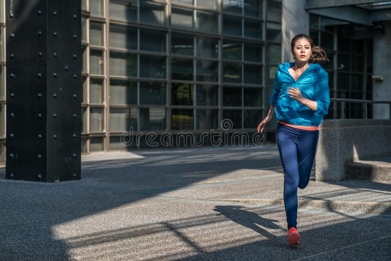 Woman jogging in sport clothes on urban road. royalty free stock photos