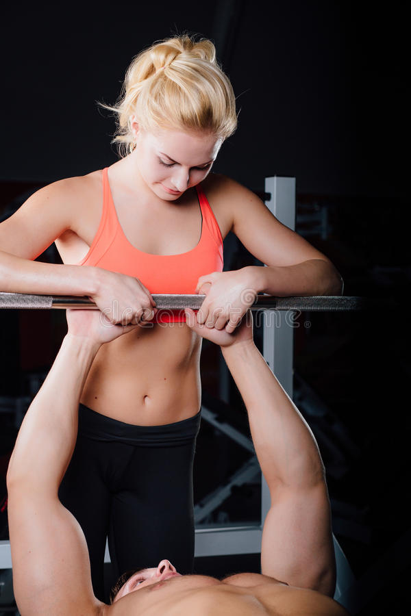 Sport, fitness, teamwork, weightlifting and people concept - young girl personal trainer work with man barbell stock image