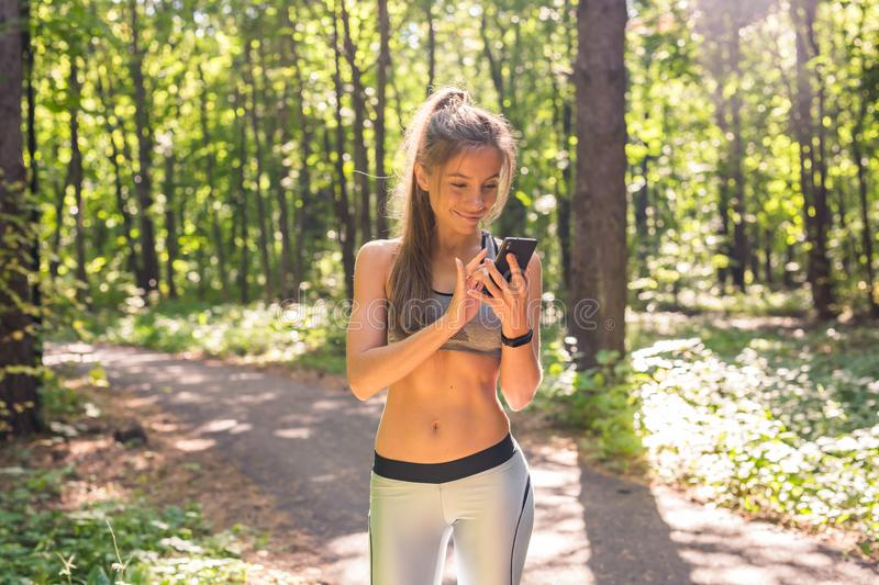 Sport, fitness, technology and people concept - young woman athlete with heart rate watch or fitness bracelet or tracker. Woman with heart-rate watch or fitness royalty free stock photography