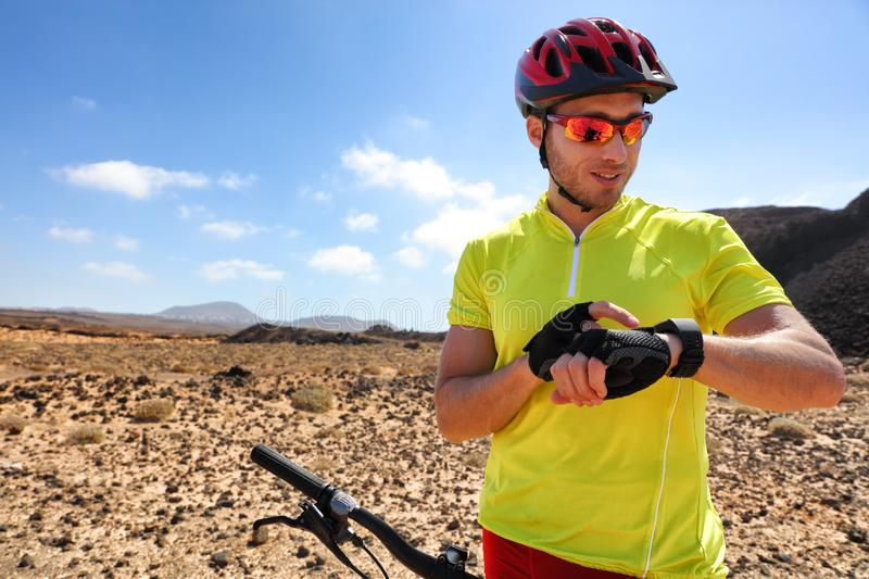 Sport fitness watch mountain biker on mtb bike using smartwatch app for fitness challenge. Young man athlete using his wearable stock photos