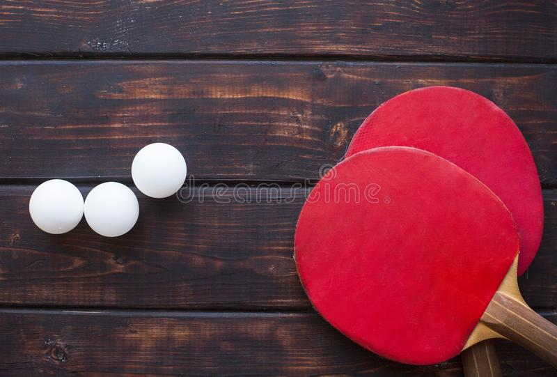 Sport fitness, weight loss concept. Ping pong racket, balls on dark wooden background. Vintage retro instagram filter royalty free stock images