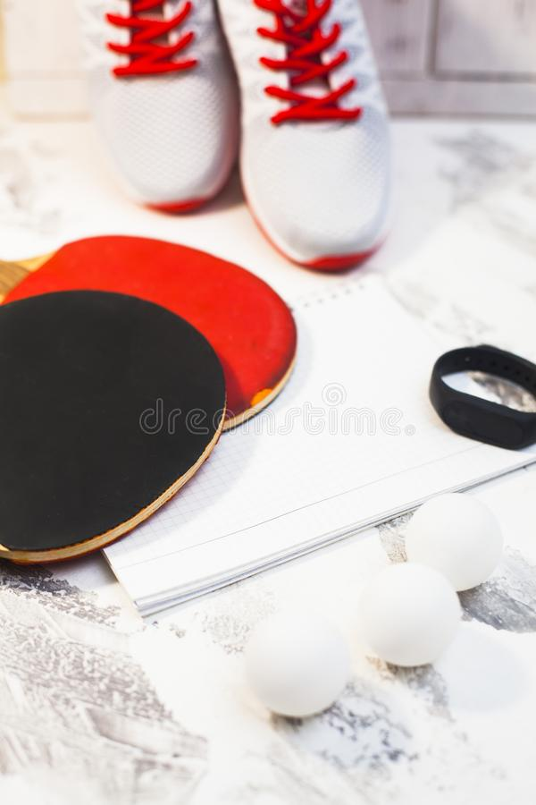 Sport fitness, weight loss concept. Ping pong racket, balls, notepad, sneakers on white wooden background. Vintage retro instagram filter royalty free stock photos