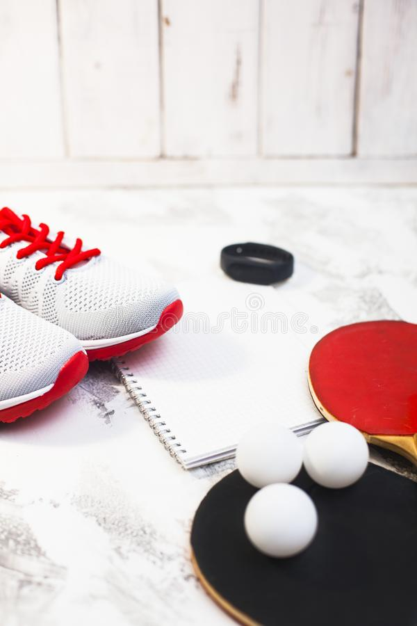 Sport fitness, weight loss concept. Ping pong racket, balls, notepad, sneakers on white wooden background. Vintage retro instagram filter stock photo