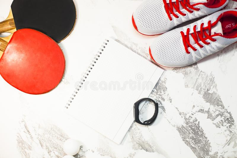 Sport fitness, weight loss concept. Ping pong racket, balls, notepad, sneakers on white wooden background. Vintage retro instagram filter royalty free stock image