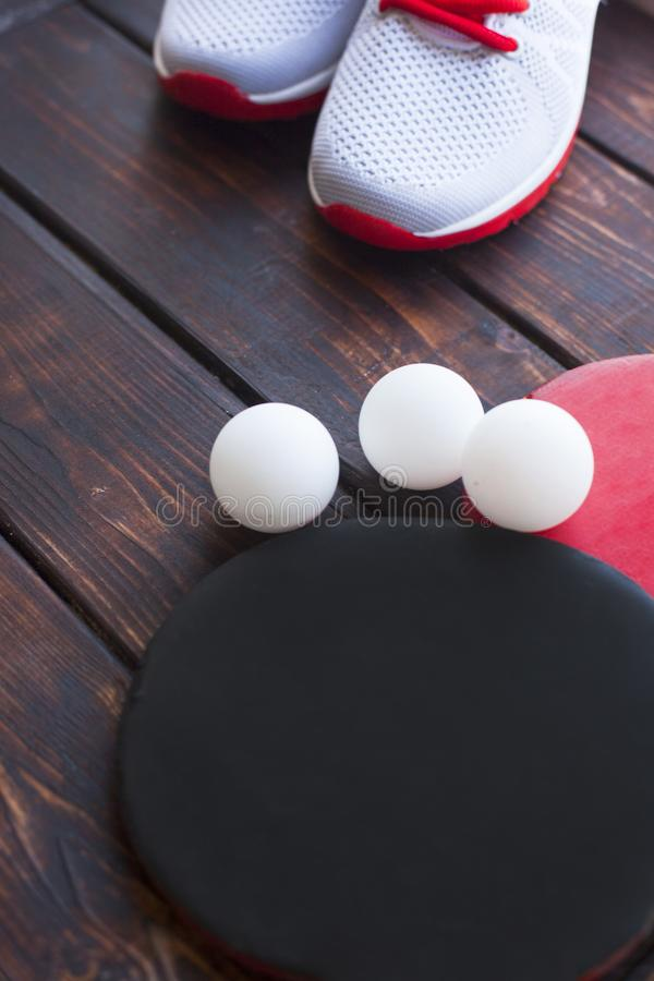 Sport fitness, weight loss concept. Ping pong racket, balls, sneakers on dark wooden background. Vintage retro instagram filter royalty free stock photo