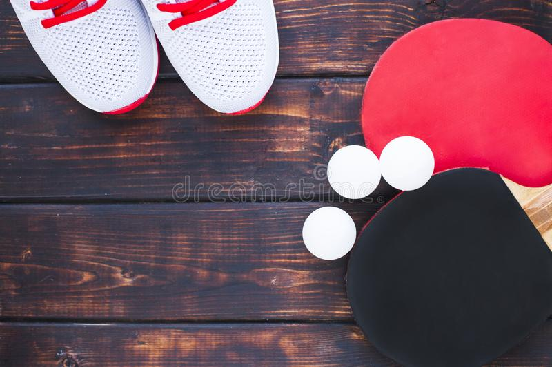 Sport fitness, weight loss concept. Ping pong racket, balls, sneakers on dark wooden background. Vintage retro instagram filter royalty free stock image