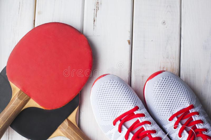 Sport fitness, weight loss concept. Ping pong racket, balls, sneakers on white wooden background. Vintage retro instagram filter royalty free stock photos
