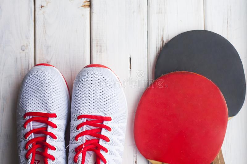 Sport fitness, weight loss concept. Ping pong racket, balls, sneakers on white wooden background. Vintage retro instagram filter royalty free stock images
