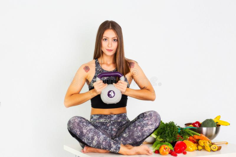 Sport fitness woman, fitness woman leggings,Young beautiful girl with long brown hair in a sports top and tights with fruits and. Sport fitness woman leggings stock photo