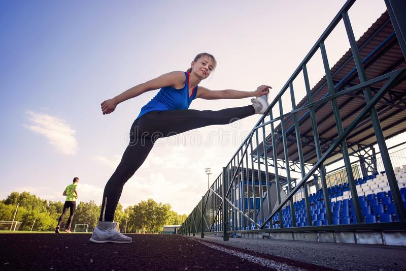Sport fitness woman stretching on the stadium. Sport blonde girl stretching arms in sport running arena with many tracks. Summer m royalty free stock photos