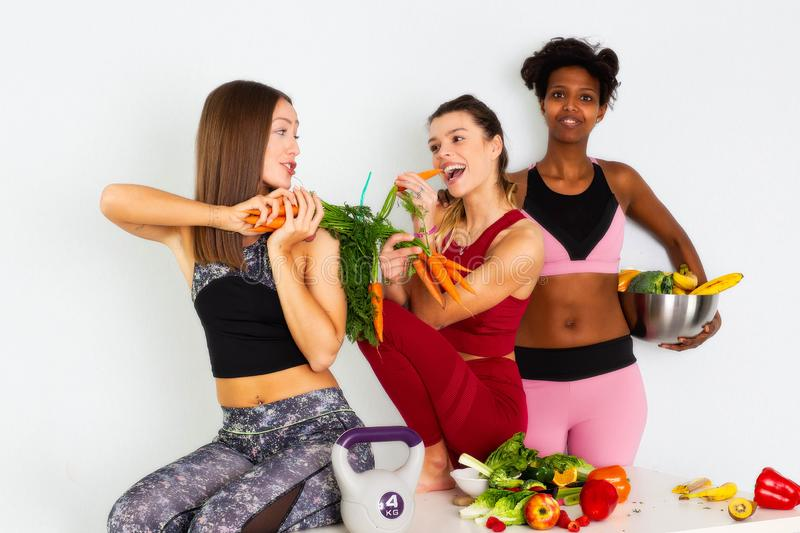 Sport fitness women,fitness women leggings,Young beautiful girl with long brown hair in a sports top and black model with fruits. Sport fitness women leggings stock photography