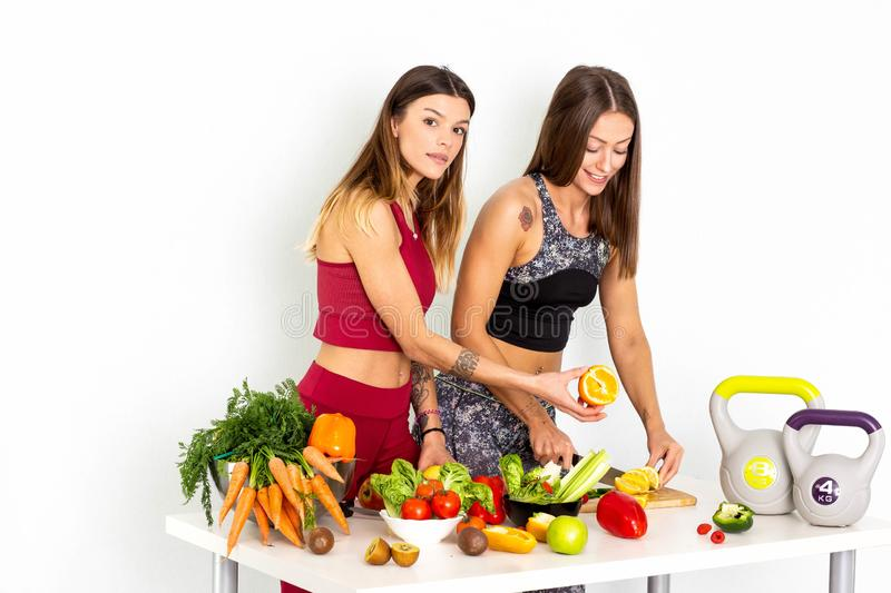 Fitness Women Cuting Orange Stock Images And Stock Footage. Sport fitness women leggings,Young beautiful girl with with sports top and tights with fruits and stock photo