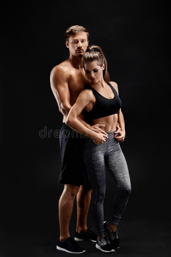 Sport, fitness, workout concept. Fit couple, strong muscular man and slim woman posing on a black background. Sport, fitness, workout concept. Fit couple, strong stock photos