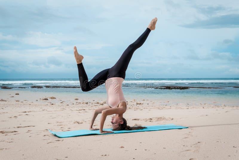 Sport, fitness, yoga, mensen en gezondheidsconcept - het jonge vrouw doen headstand oefent op strandachtergrond uit stock afbeeldingen