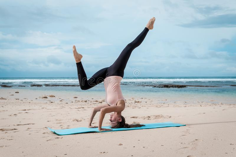 Sport, fitness, yoga, people and health concept - young woman doing headstand exercise on beach background stock images