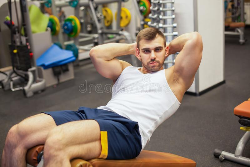 Sport, forme physique, bodybuilding, mode de vie et concept de personnes - le jeune homme faisant le banc abdominal d'exercices d photo stock