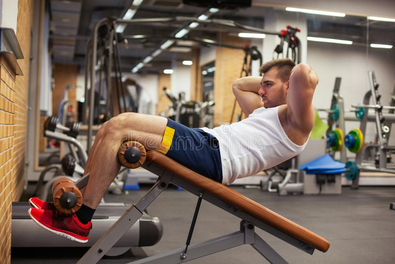 Sport, forme physique, bodybuilding, mode de vie et concept de personnes - le jeune homme faisant le banc abdominal d'exercices d images stock