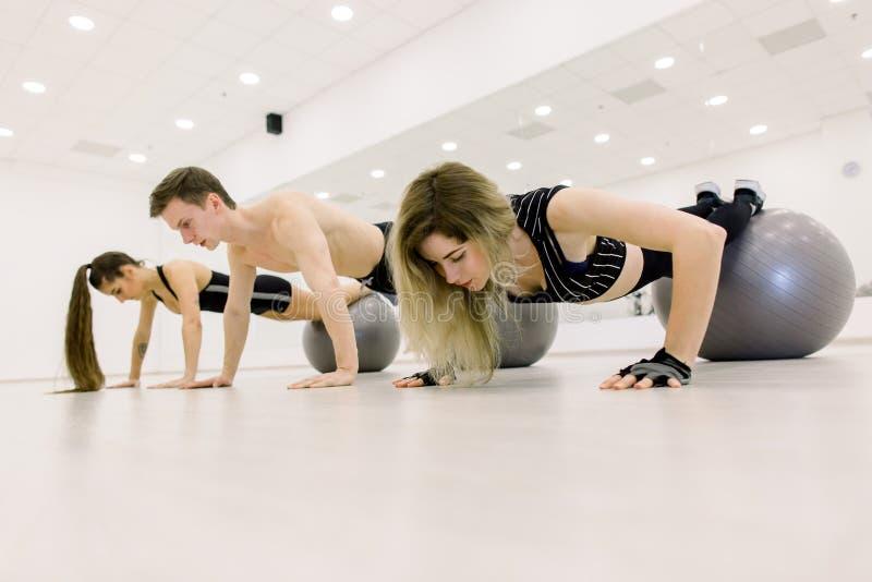 Sport, forme physique, mode de vie et concept de personnes - homme de sourire et deux femmes établissant avec la boule d'exercice image stock