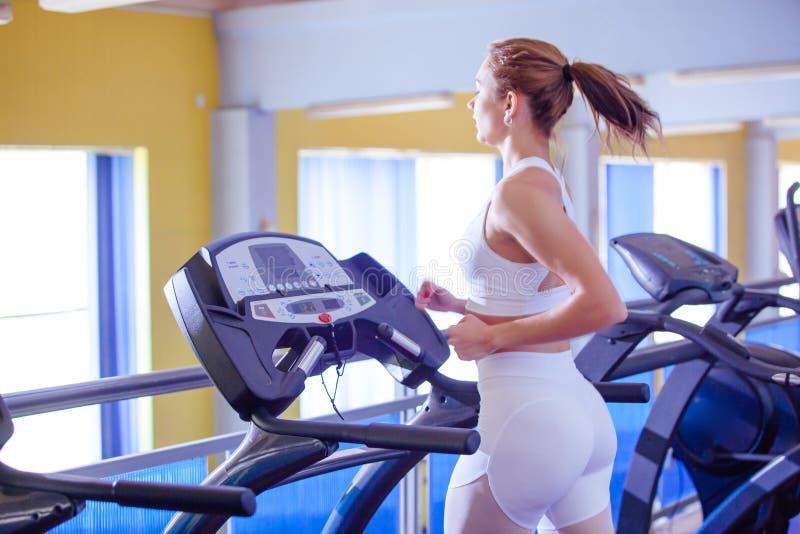 Sport, forme physique, mode de vie, technologie et concept de personnes - jeune femme courant sur le tapis roulant photo stock