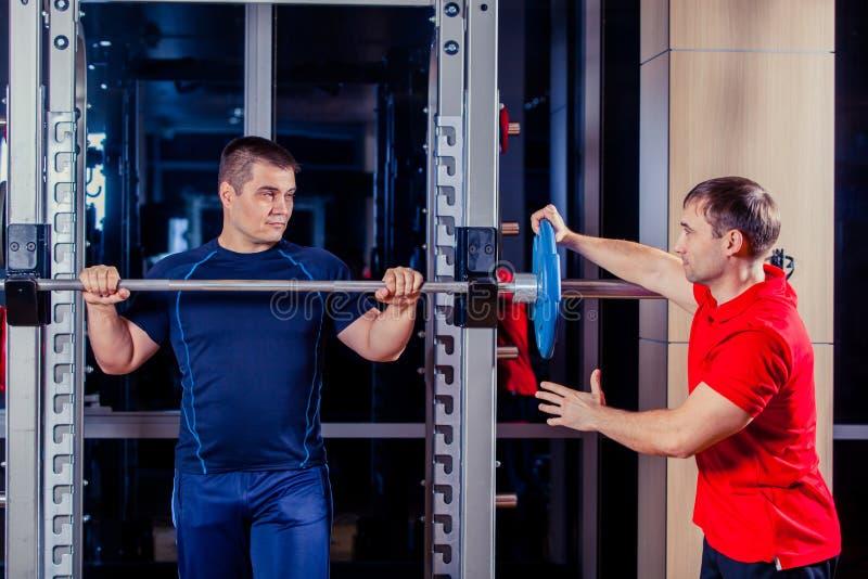 Sport, forme physique, travail d'équipe, concept de personnes de bodybuilding - homme et entraîneur personnel avec le barbell flé photo stock