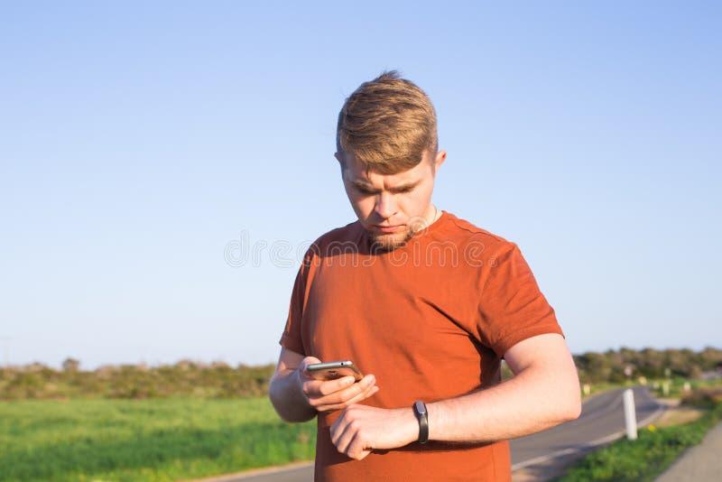 Sport, gadżet, aktywność tropiciel i ludzie pojęć, - Męskiego biegacza jogging outside patrzeje jego noszoną sprawność fizyczną zdjęcia royalty free