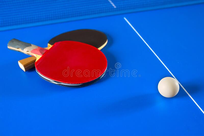 Sport games in Ping Pong. Rackets for table tennis and a ball on the blue table royalty free stock photography