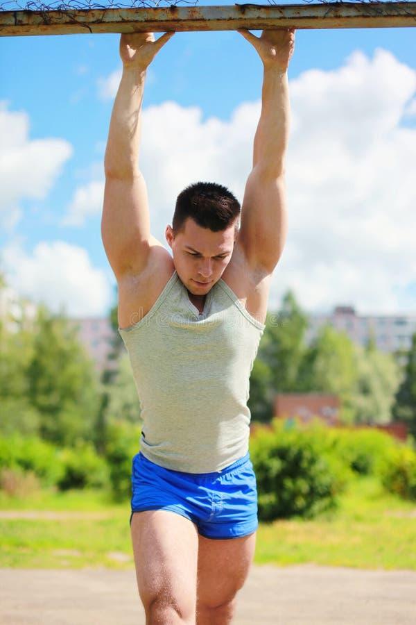 Sport gatagenomkörarebegrepp - idrottsman på horisontalstången arkivfoto