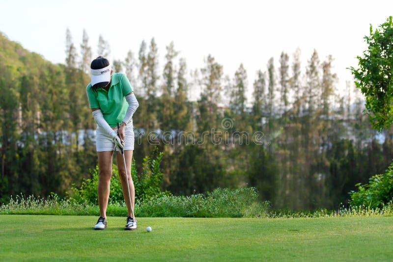 Sport gesund Asiatischer sportlicher Frauenfokus des Golfspielers, der im Urlaub Golfball am gr?nen Tag des Golfs setzt lizenzfreie stockfotografie