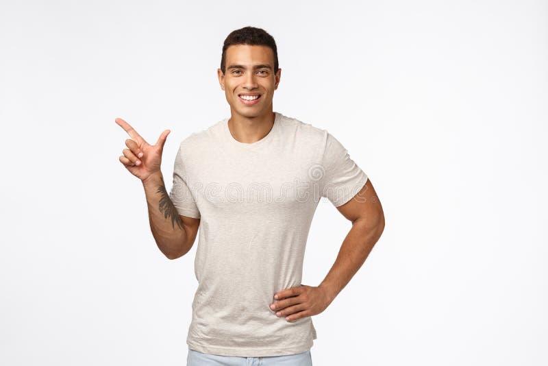 Sport, gesunde Menschen und Bewegungskonzept Ein ansprechender, lächelnder Hispanic-Typ in lockerem T-Shirt, halten Sie Hand auf  lizenzfreie stockfotos