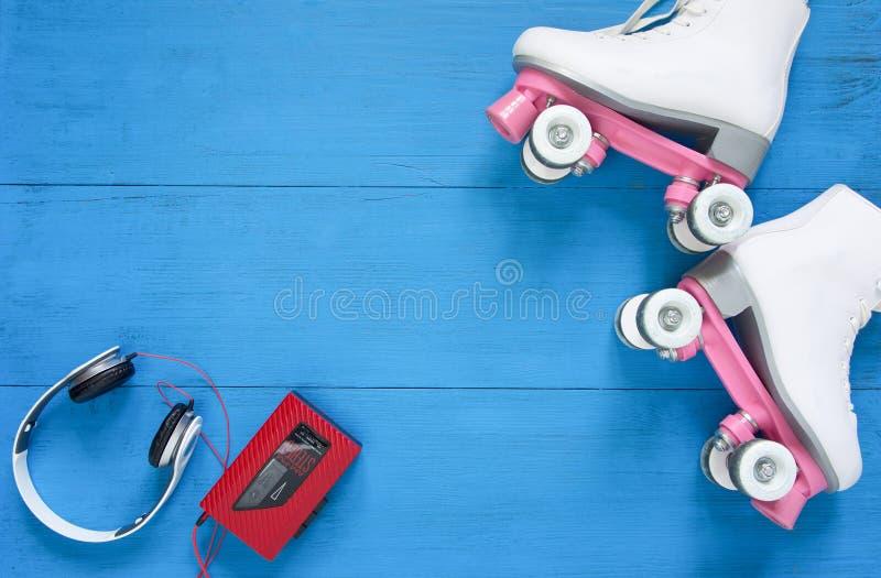 Sport, gezonde levensstijl, rol het schaatsen achtergrond Witte rolschaatsen, hoofdtelefoons en uitstekende bandspeler Vlak leg,  stock afbeeldingen