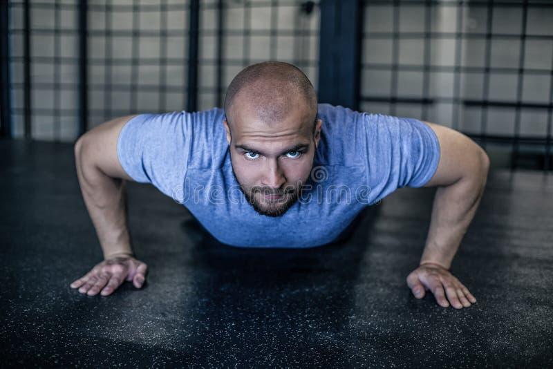 sport Giovane uomo atletico che fa spinta-UPS Esercitazione muscolare e forte del tipo vestito in un'uniforme di sport immagini stock
