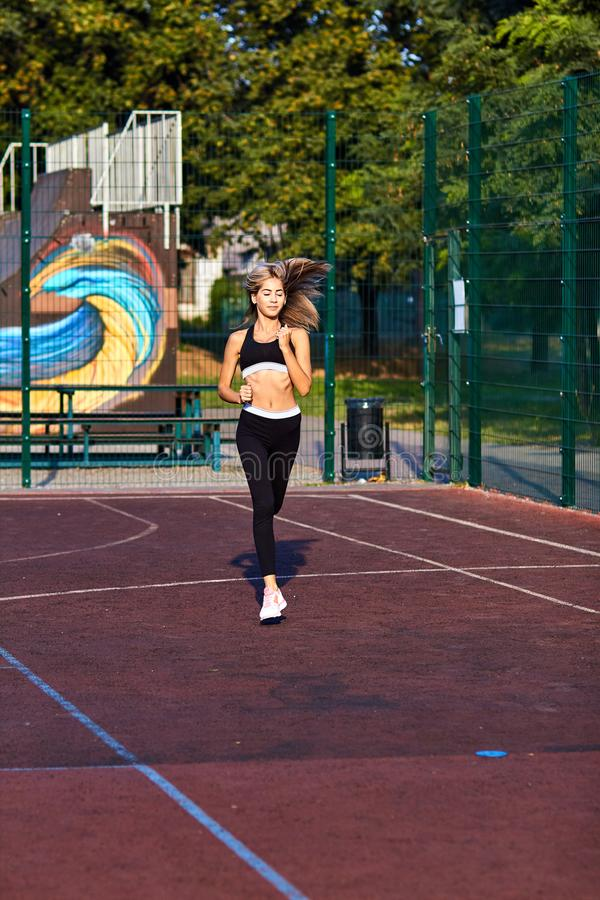 Sport girl. The girl is doing fitness exercises. Beautiful young sports woman doing exercises. A woman is training on a sports fie. Ld. Young beautiful girl in stock photos
