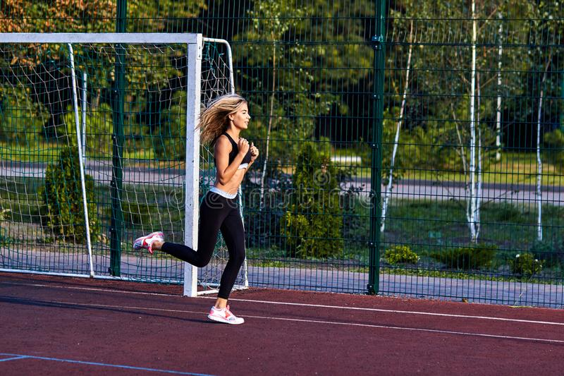 Sport girl. The girl is doing fitness exercises. Beautiful young sports woman doing exercises. A woman is training on a sports fie. Ld. Young beautiful girl in stock photo