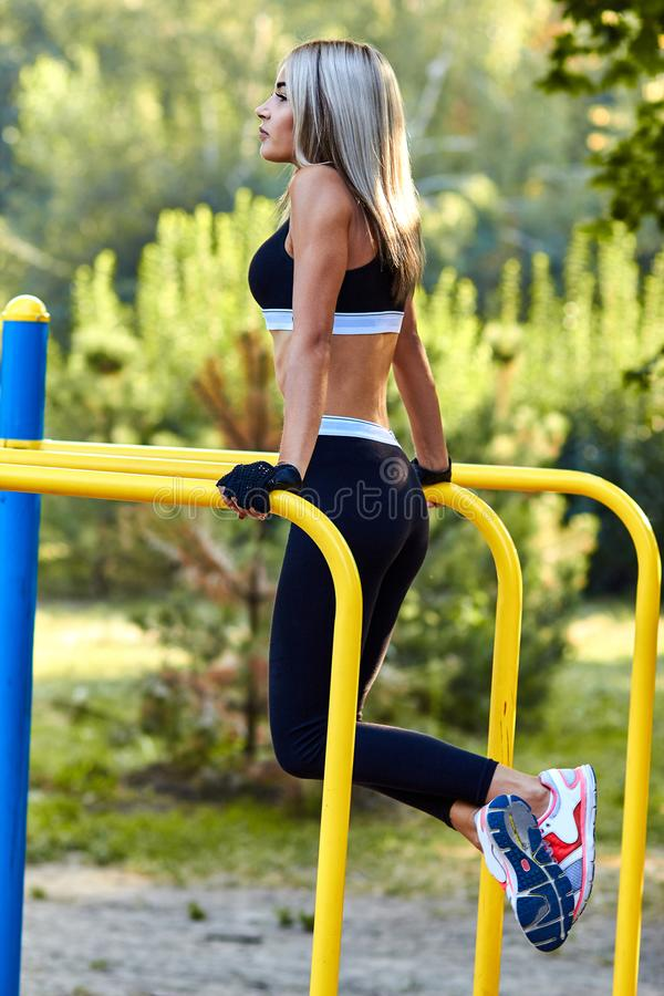 Sport girl. The girl is doing fitness exercises. Beautiful young sports woman doing exercises. A woman is training on a sports fie. Ld. Young beautiful girl in royalty free stock images