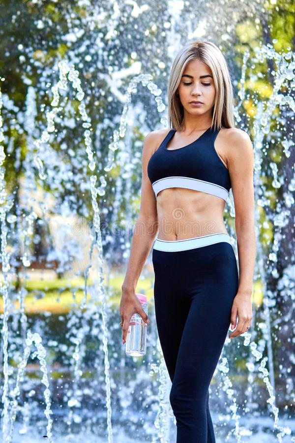Sport girl. The girl is doing fitness exercises. Beautiful young sports woman doing exercises. A woman is training on a sports fie. Ld. Young beautiful girl in royalty free stock photo
