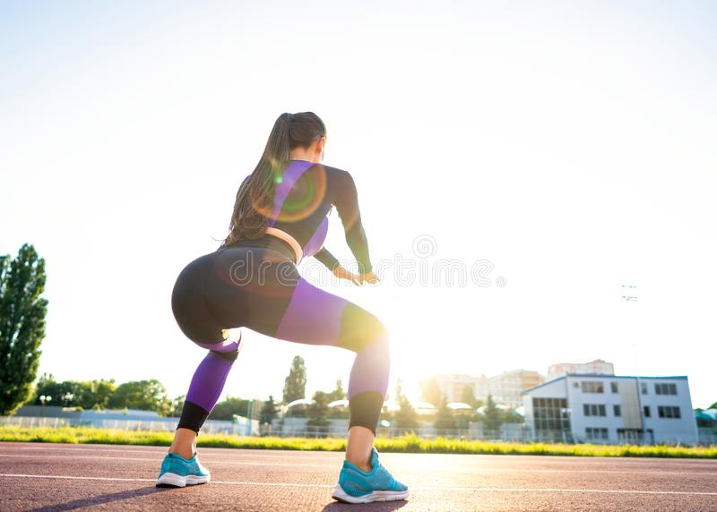 Sport girl engaged in a warm-up at the stadium at sunset.  stock images