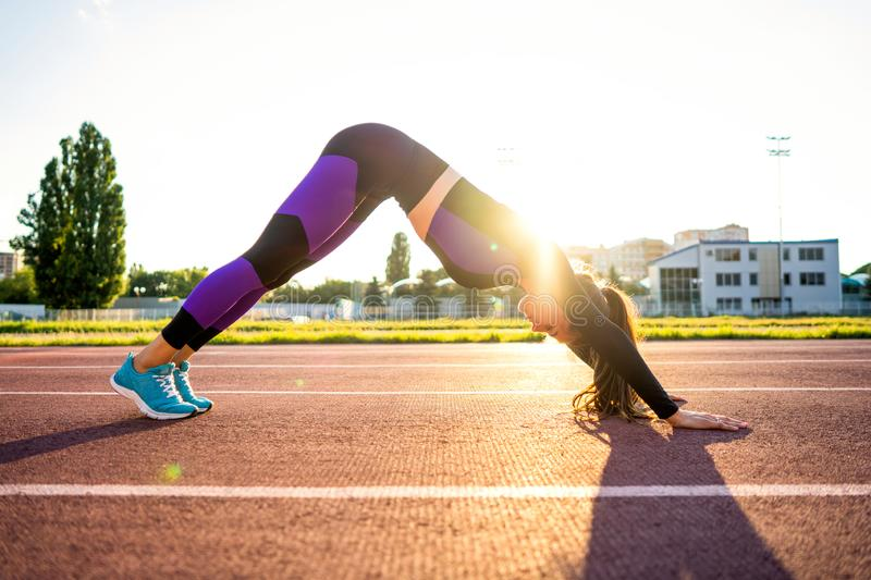 Sport girl engaged yoga in a warm-up at the stadium at sunset.  royalty free stock photo