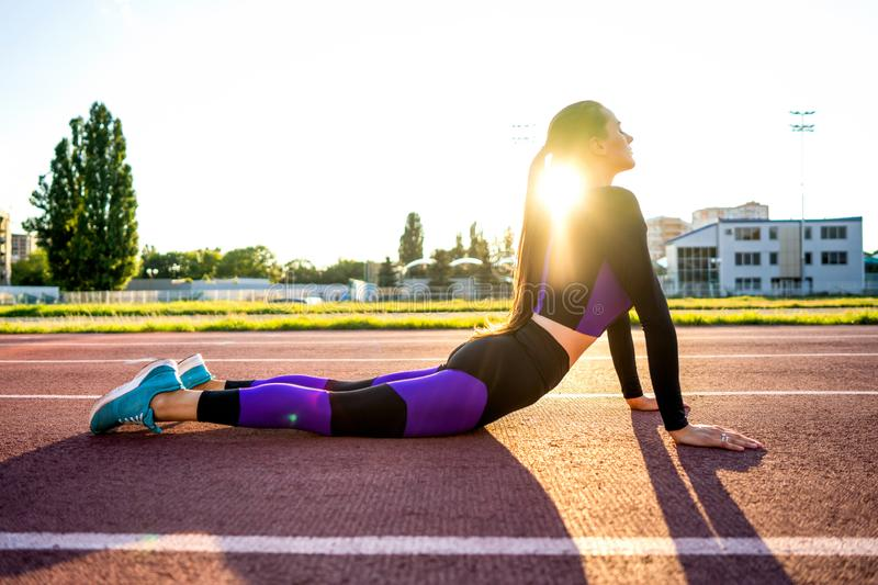Sport girl engaged yoga in a warm-up at the stadium at sunset.  stock photos