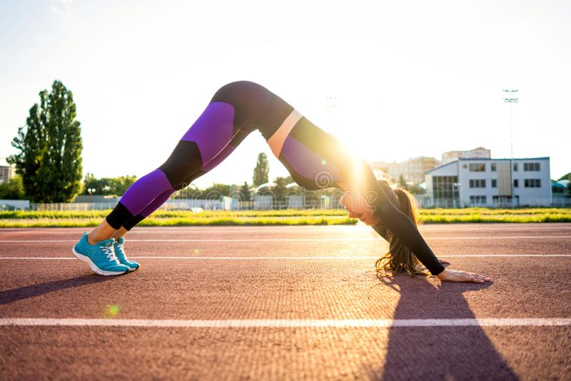 Sport girl engaged yoga in a warm-up at the stadium at sunset royalty free stock photos