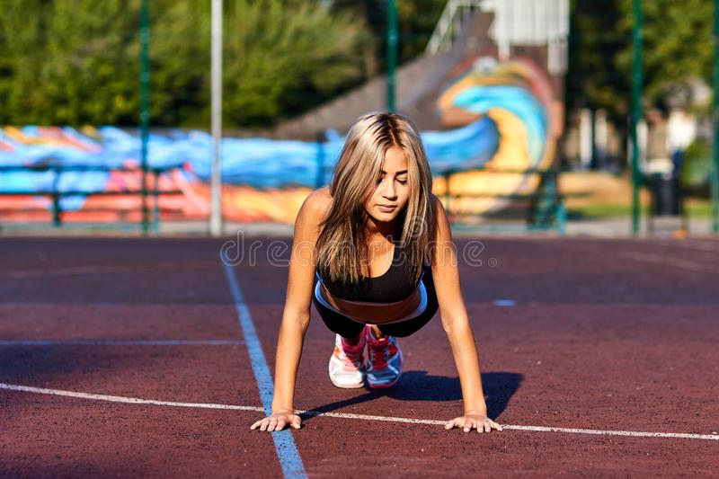 Sport girl. The girl is doing fitness exercises. Beautiful young sports woman doing exercises. A woman is training on a sports fie. Ld. Young beautiful girl in stock images