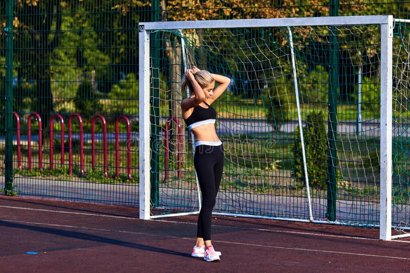 Sport girl. The girl is doing fitness exercises. Beautiful young sports woman doing exercises. A woman is training on a sports fie. Ld. Young beautiful girl in royalty free stock photography